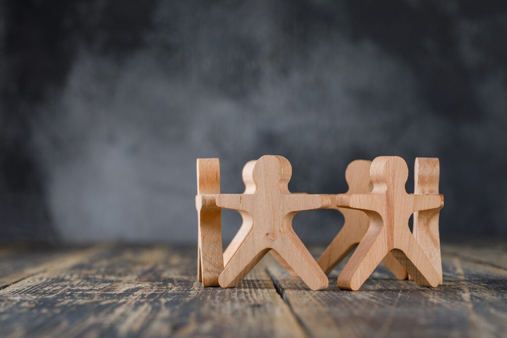 Business success and teamwork concept with wooden figures of peo