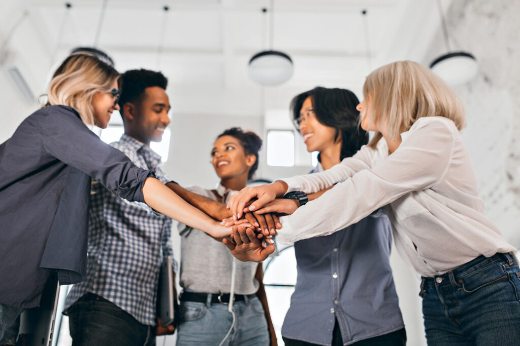 Cheerful international students with happy face expression going to work together on science project. Indoor photo of blonde woman in trendy blouse holding hands with coworkers..