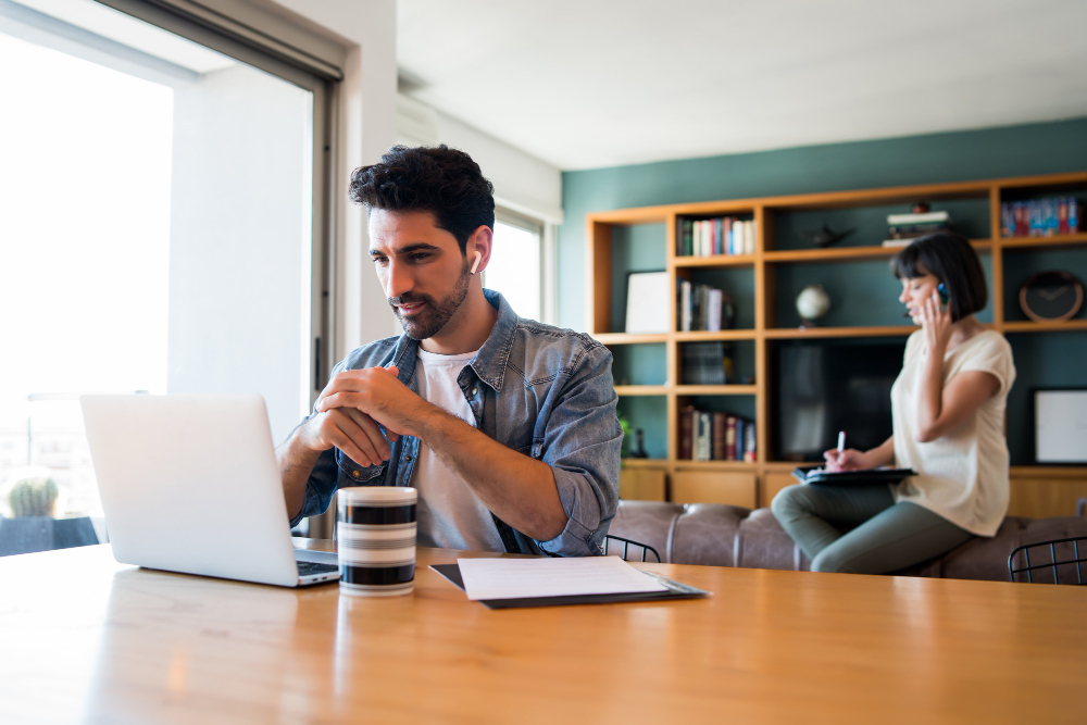 portrait-young-man-working-with-laptop-from-home-while-woman-talking-phone